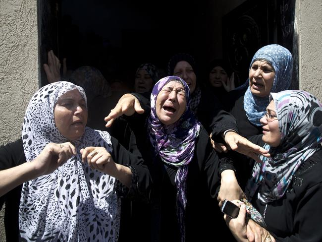 Counting the casualties ... Palestinian women mourn during the funeral of Hafez Hammad, a senior Islamic Jihad commander, and five of his family members, including two women and two children, who were all killed when an Israeli missile slammed into their house in the northern Gaza strip.
