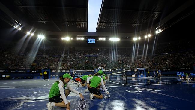 Ground staff dry the court surface at the Rod Laver Arena as rain stopped play during the first-set tiebreaker.