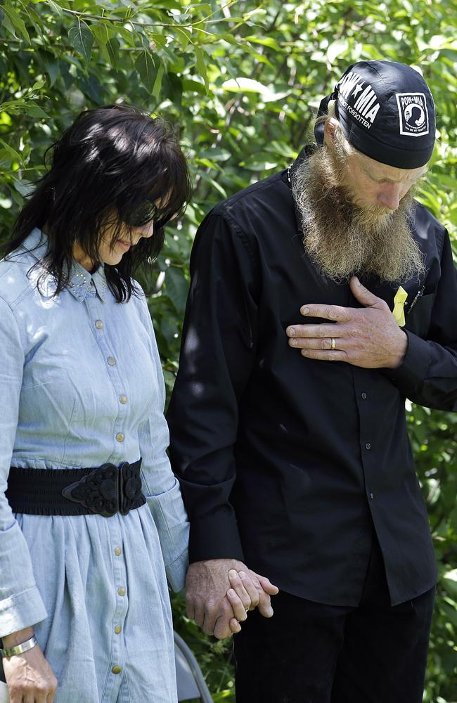 "Bob Bergdahl, right, and Jani Bergdahl, the parents of Bergdahl, hold hands as they pray at the ""Bring Bowe Back"" celebration held to honour their son."