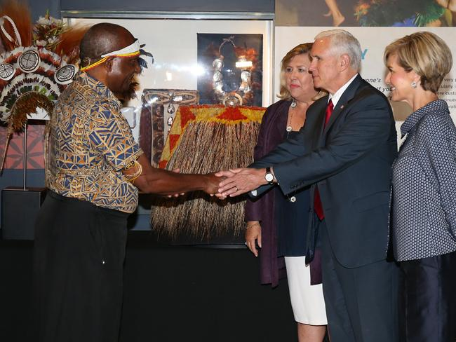 Vice President Mike Pence, with Foreign Minister Julie Bishop (right), shakes hands with Dr Michael Mel, wearing a traditional Papa New Guinea outfit, during a visit to the Australian Museum. Picture: AAP Image/David Moir