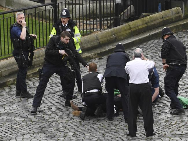 An armed police officer stands over emergency services treating the suspect outside the Palace of Westminster, London. Picture: AP