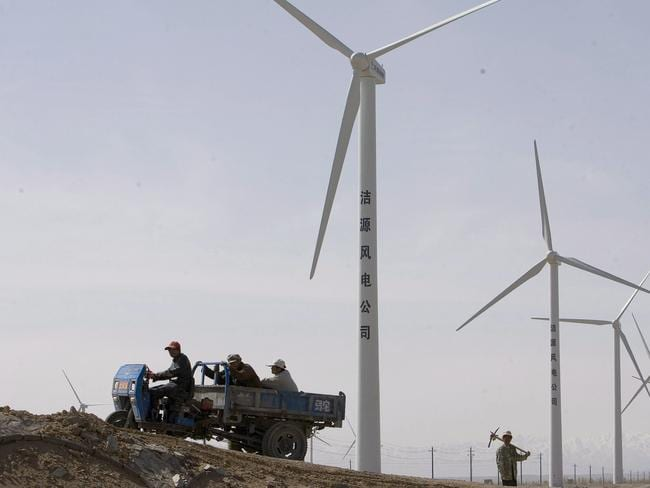 Chinese workers around windmills on the outskirts of Yumen. EPA/DIEGO AZUBEL