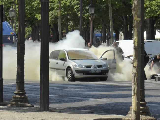 French gendarmes use fire extinguishers after a man rammed into a police convoy and detonated an explosive device on the Champs Elysees. Picture: Noemie Pfister via AP
