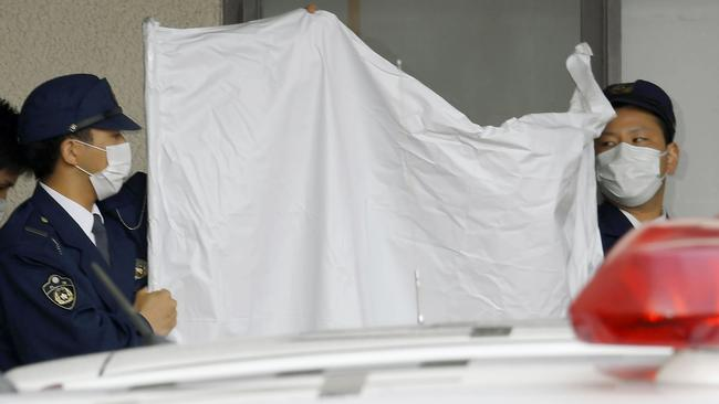 Police officers hide the face of arrested Japanese Yoshitane Yamasaki with a sheet while escorting him to a police vehicle. Picture: Yohei Nishimura/Kyodo News via AP