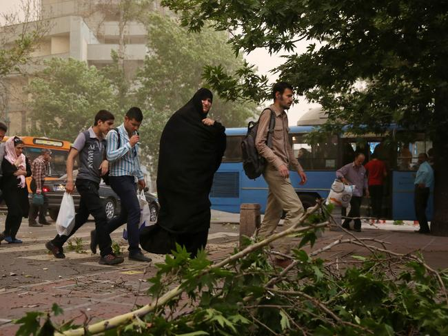 Pedestrians cross a street in Tehran after the dust storm struck, causing chaos in its wake.