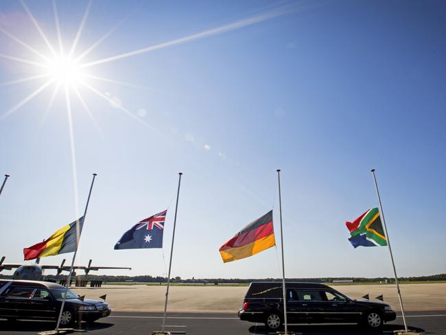 A convoy of hearses drives past flags flying at half-mast while leaving the Eindhoven Airbase / Picture: AFP