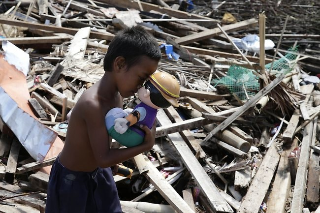 John Ay-ay, 7, kisses a toy he found from the rubble in Tacloban city, Leyte. (AP Photo/Bullit Marquez)