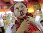 "In this Saturday, Oct. 17, 2015, photo, a devotee to the Chinese Shrine Ban Tha Rue in Phuket, Thailand, goes into a trance with her tongue and face pierced prior to a street procession. The annual Vegetarian Festival and its accompanying sacred rituals are believed to bestow good fortune on those who practice the religious rites. During the nine day festival in Phuket Town and surrounding communities which are made up mainly of Chinese descendants, residents observe a strict vegetarian or vegan diet that is believed to cleanse the body and grant merit. Sacred rituals where men and women devotees known as ""Mah Song"" or ""Spirit Horses"", work themselves into trances to have all manner of knives, daggers, swords or other items pierced through their cheeks. It is believed that they experience no pain while in the trance. Picture: AP Photo/David Longstreath"