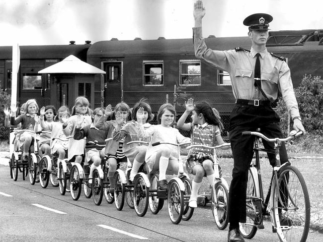 A police officer cadet teaches Mitchell Park Infant School students road safety at Thebarton, 1970.