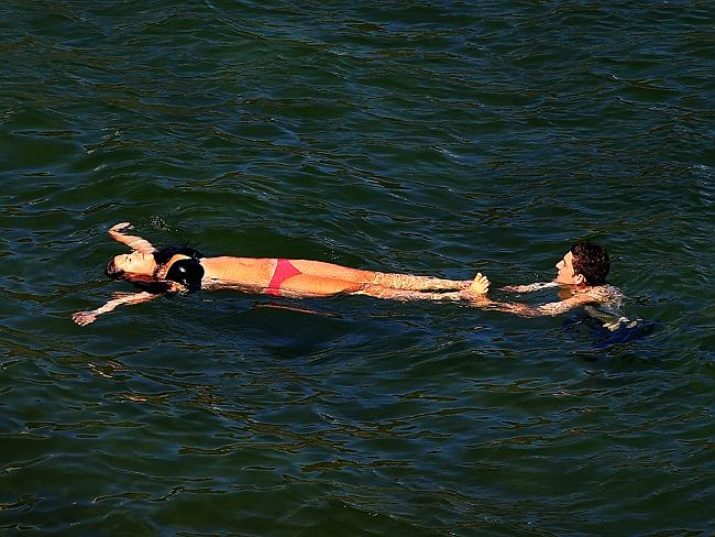 A couple relax in the water at Gordons Bay.