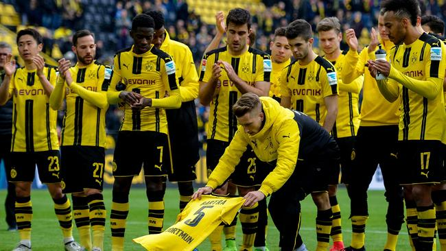 Dortmund's Marco Reus lays down the shirt of Marc Bartra in front of the Yellow Wall.