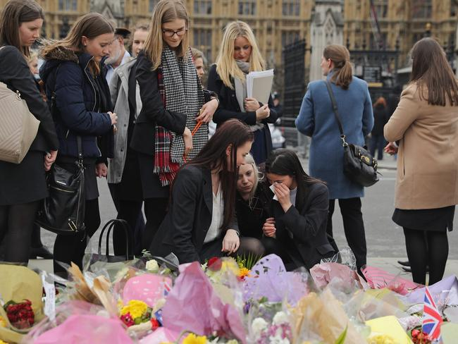LONDON, ENGLAND - MARCH 29: People look at floral tributes left for the victims of last week's Westminster terrorist attack on March 29, 2017 in London, England. Faith Leaders head up a vigil including members of the public and police officers on Westminster Bridge exactly one week after Khalid Masood ploughed a hired car into people crossing Westminster Bridge, killing three. Masood gained entry to the grounds of the Houses of Parliament stabbing PC Keith Palmer to death before he was shot dead by armevd police. (Photo by Dan Kitwood/Getty Images)