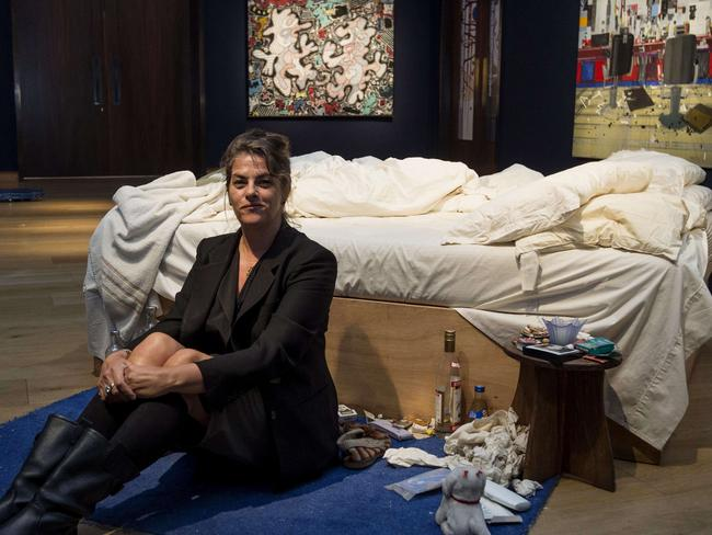 "British artist Tracey Emin sits on her iconic art installation, ""My Bed"" during a press preview at Christie's auction house."