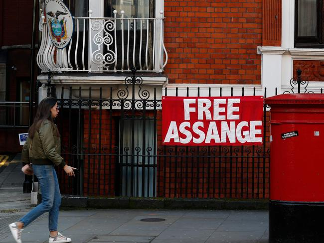"A woman walks past a sign that reads ""free Assange"" on the facade of the Ecuadorean Embassy in London. Picture: AFP"