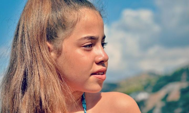 Close up portrait of a beautiful tanned teenager girl by the swimming pool