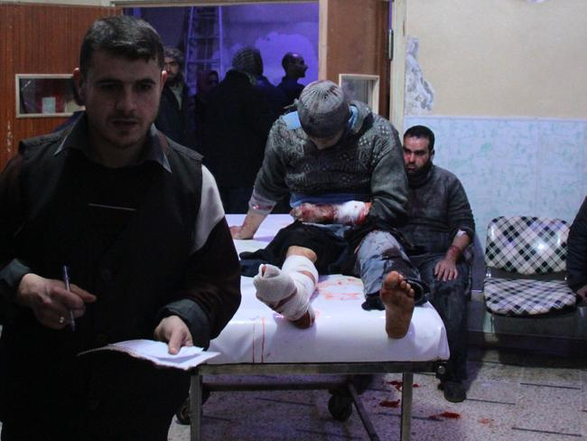 A wounded Syrian man sits on a gurney as victims pour into a makeshift hospital in the rebel-held town of Douma, following air strikes by regime forces on the besieged Eastern Ghouta region on the outskirts of Damascus. Picture: Hamza Al-Ajweh/AFP