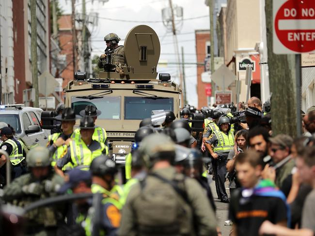 A Virginia State Police officer in riot gear keeps watch from the top of an armoured vehicle after a car drove through a crowd of counter-demonstrators during a race hate march. Picture: Chip Somodevilla/Getty Images/AFP