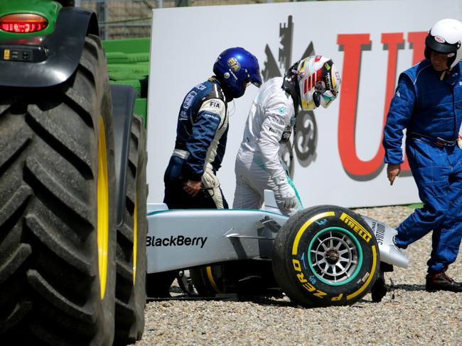 Lewis Hamilton of Great Britain and Mercedes GP gets out of his car after crashing.