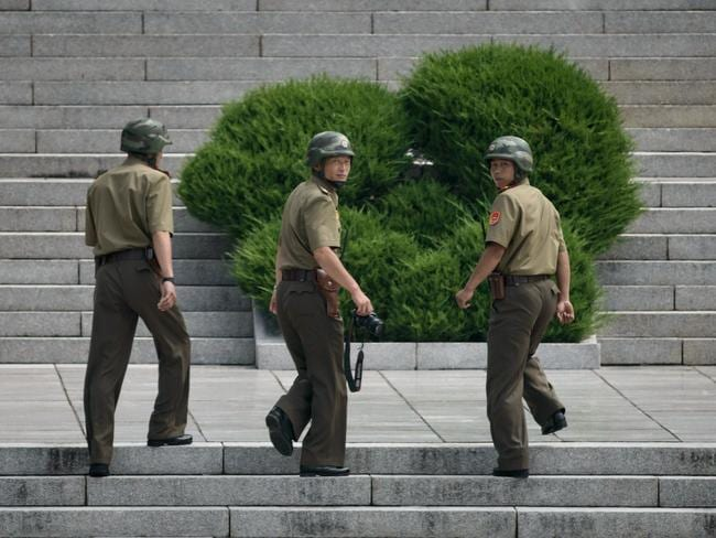 North Korean soldiers walk up the stairs to the Panmungak building opposite the military demarcation line separating North and South Korea. Tourists are forbidden from photographing soldiers.