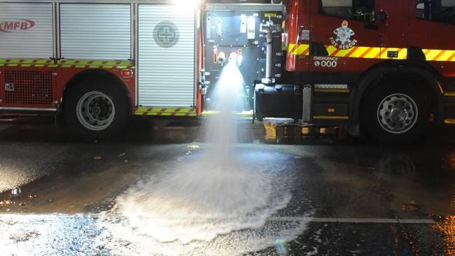 Metropolitan Fire Brigade officers pump out the basement of the Supreme Court on the corner of Lonsdale and Queen Streets after it flooded. Picture: Andrew Henshaw
