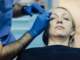 Doctor wears blue surgery gloves injecting hyaluronic acid under patients skin on forehead to fix facial wrinkles. Face Lifting Treatment. Patient is mature adult woman in her early 40s. Selective focus to woman's face. Real process has been shot. Canon EOS 5Ds.