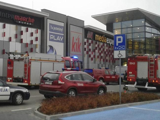 Police and firefighters' cars and trucks stand in front of the VIVO! shopping mall where a 27-year-old man attacked people with a knife killing one person and injuring several others in Stalowa Wola, southeastern Poland, on Friday, Oct. 20, 2017. (AP Photo/Rafal Baran)
