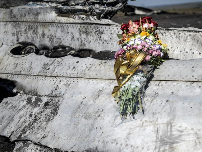 Crash site ... Flowers left by parents of an victim of the crash laid on a piece of MH17, near the village of Grabovo. Picture: Bulent Kilic