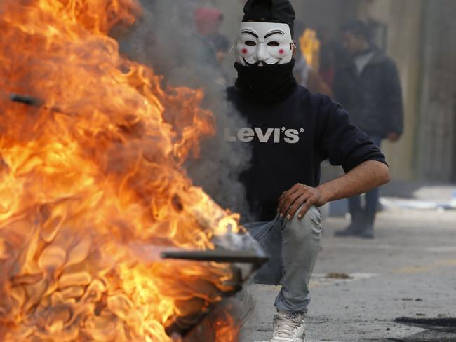 A Palestinian protester wears a Guy Fawkes mask used by the anonymous movement during clashes with Israeli troops in Hebron. Picture: AFP PHOTO / HAZEM BADER