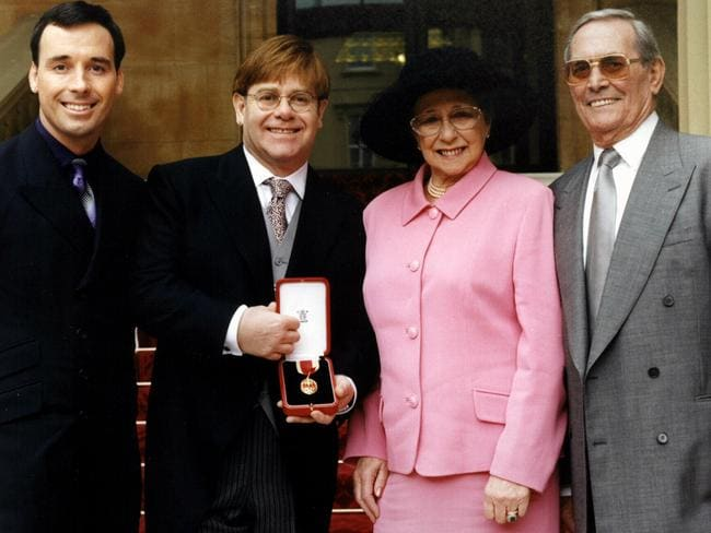 Happier times ... Elton John (2nd L) with David Furnish (L), mother Sheila & stepfather Fred Fairebrother outside Buckingham Palace in 1998 after being knighted by Queen. Picture: Supplied