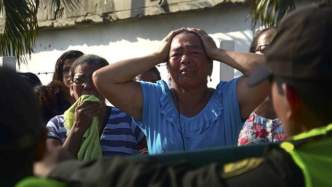 Agonising wait ... Relatives of inmates outside the Modelo jail in Barranquilla, Colombia, wait for news on the fate of loved ones.