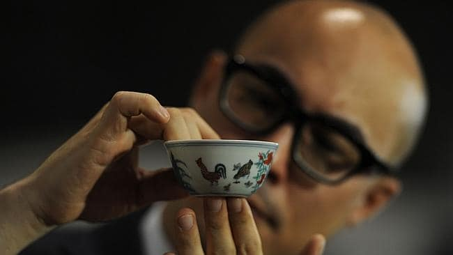 Dont drop it... The Meiyintang Chenghua 'Chicken Cup' is displayed by deputy chairman for Sotheby's Asia Nicolas Chow after it was sold for a record price in Hong Kong. Picture: Aaron Tam