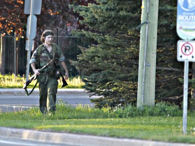 Alleged triple murderer ... Justin Bourque walks on Hildegard Drive in Moncton, New Brunswick, after several shots were fired in the area and three RCMP were killed.