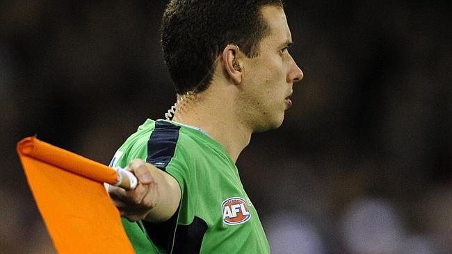 An AFL umpire holds the flag up to signal an interchange breach