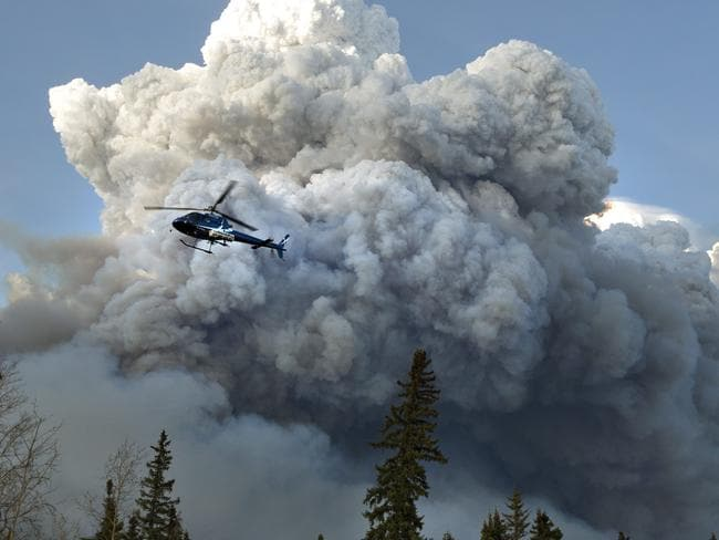 A helicopter flies past a wildfire in Fort McMurray, Alberta. Picture: Jason Franson /The Canadian Press via A