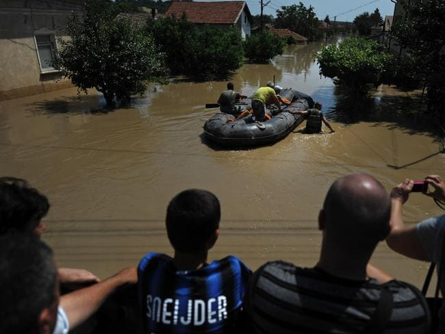 Onlookers ... spectators watch as a rescue boat evacuates people in Mizia, Bulgaria after flooding caused by torrential rains. Picture: Nikolay Doychinov