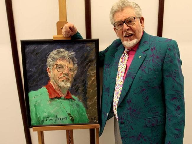 Two-faced deviant ... Rolf Harris with his self portrait at the National Portrait Gallery in 2008. The gallery has removed the painting from view since the star's perverted secrets were revealed.