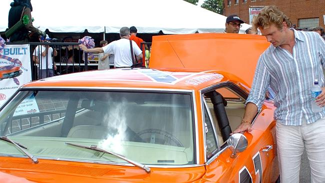 """John Schneider looking at replica of """"General Lee"""" motor car from TV programme ..."""