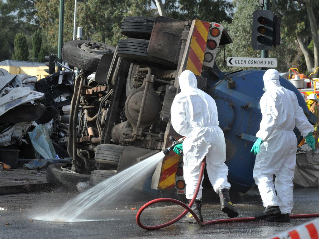 Hazmat crews hose down Glen Osmond Rd after a septic-waste truck crashed into stationary cars. Picture: Roger Wyman