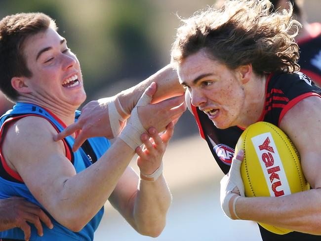 Joe Daniher is tackled by Zac Merrett. Photo by Michael Dodge