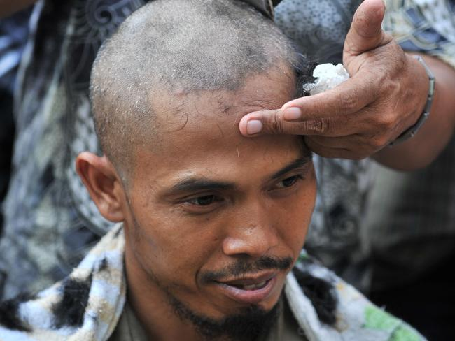 An Indonesian supporter of presidential candidate Joko Widodo and running mate Jusuf Kalla shaves his head to celebrate Widodo's victory Pic: AFP/ADEK BERRY