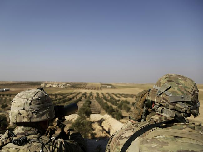 American troops looking over a battlefield from a small outpost in northern Syria. Picture: AP