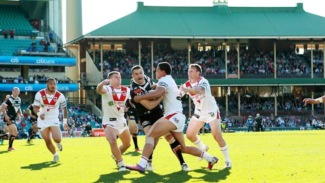 Tiger James Tedesco is tackled by Dragons players during a clash at the SCG.