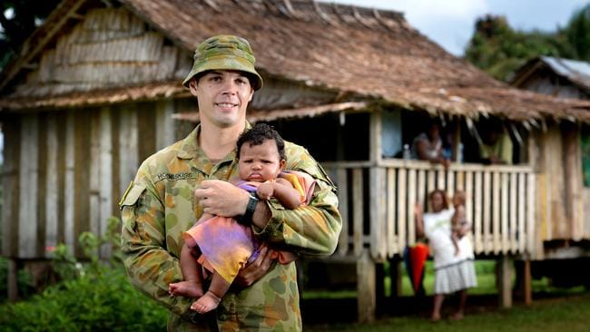 Operation Anode ... Army Corporal Phil Hodgskiss with local baby Alindha Bernadette in the Solomon Islands in 2013.