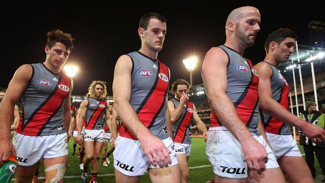 Dejected Essendon players walk off the MCG after losing to Richmond by 18 points.