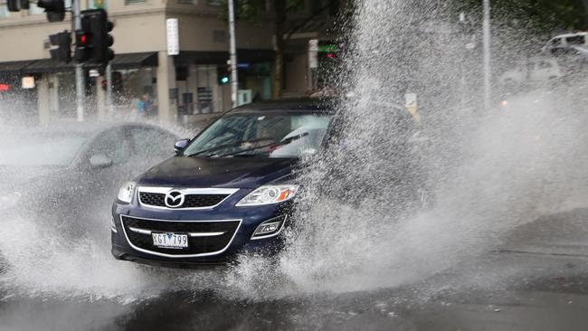 The downpour at the corner of Exhibition and Flinders Street. Picture: David Crosling
