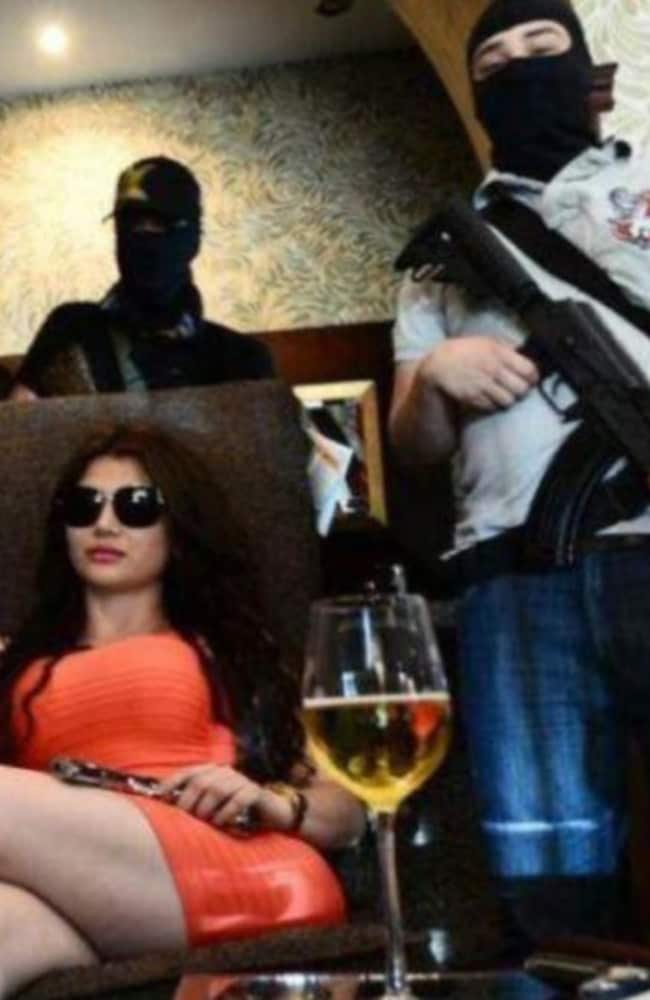 Loud and proud ... Claudia Ochoa Felix holds a gun while sitting down with a glass of wine near another man with a rifle. Picture: Supplied.