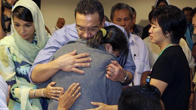 Hardest part... Malaysia's Defence and acting Transport Minister Hishammuddin Hussein, centre, comforts a relative. Picture: AP