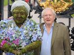 David Attenborough poses with a floral sculpture of himself outside the Royal Botanical Gardens at Kew Gardens on May 17, 2012 in London, England. The sculpture was created by RHS Chelsea Flower Show Gold Medallist winner Joe Massie. (Photo by Stuart Wilson/Getty Images,)