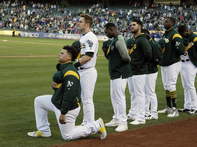 Oakland Athletics catcher Bruce Maxwell kneels during the National Anthem.