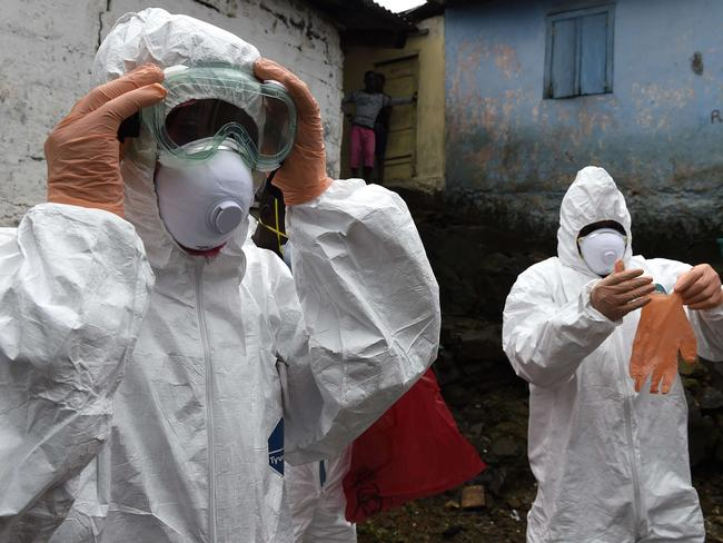 Safety first ... Medical staff members of the Croix Rouge NGO put on protective suits before collecting the corpse of a victim of Ebola in Monrovia. Pic: AFP PHOTO / PASCAL GUYOT